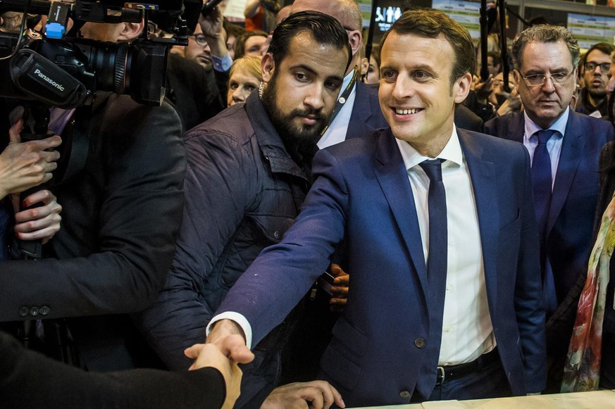 epa06907398 The then French presidential candidate Emmanuel Macron (C-R) of the 'En Marche' political movement flanked by security staff Alexandre Benalla (C-L) visiting the International Agriculture Fair in Paris, France, 01 March 2017 (reissued 24 July 2018). A video has been released on 19 July 2018, allegedly showing Alexandre Benalla, French President Emmanuel Macron's deputy chief of staff, wearing a riot helmet and police uniform, while attacking protesters during street demonstrations on 01 May 2018. Media reports on 24 July state that Benalla has been fired and the prosecution is officially investigating the case. EPA/CHRISTOPHE PETIT TESSON