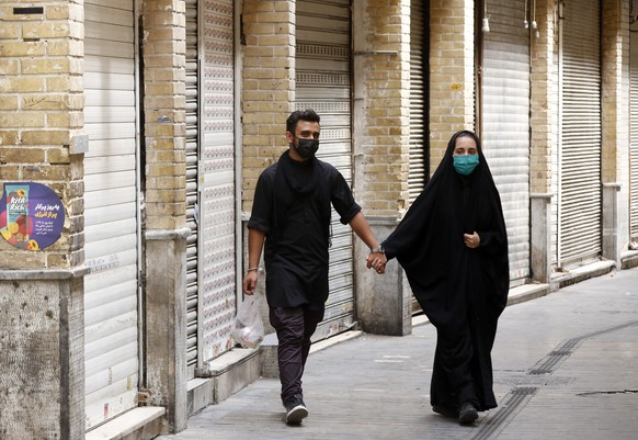 epa09416226 An Iranian couple wearing face masks walk next to closed shops in Tajrish old bazaar in Tehran, Iran, 16 August 2021. Iranian authorities began a one-week lockdown, from 16 August until 21 August 2021, to slow the spread of the Covid-19 and Delta variant in Iran as the country faces a fifth wave of the coronavirus crisis. According to the Iranian health ministry, Iran recorded its highest COVID-19 death toll by reporting 655 victims in the past 24 hours.  EPA/ABEDIN TAHERKENAREH