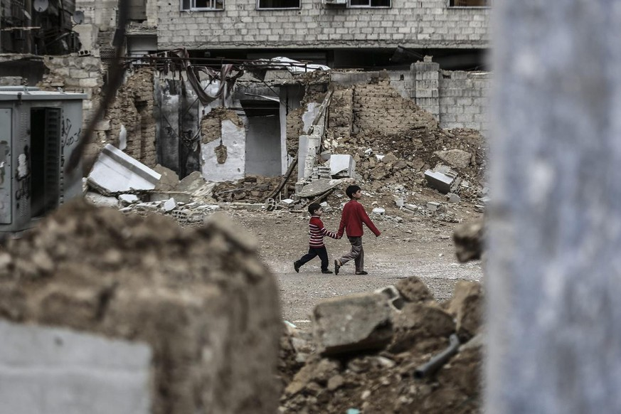 epa04995259 Two young Syrian boys hold hands as they walk past destroyed houses in rebel-held area of Douma, outskirts of Damascus, Syria, 25 October 2015. More than 250,000 people have died in the Syrian conflict, according to estimates by the United Nations. The conflict broke out in 2011 as protests against al-Assad's rule devolved into violence after a heavy-handed crackdown by authorities. EPA/MOHAMMED BADRA