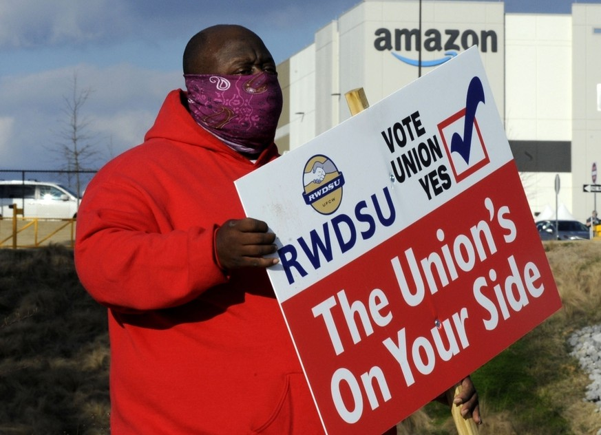 FILE - In this Tuesday, Feb. 9, 2021, file photo, Michael Foster of the Retail, Wholesale and Department Store Union holds a sign outside an Amazon facility where labor is trying to organize workers in Bessemer, Ala. Nearly 6,000 Amazon warehouse workers in Bessemer are deciding whether they want to form a union, the biggest labor push in the online shopping giant's history. Mail-in voting started in early February. Ballots must be received by the end of Monday March 29, 2021. The National Labor Relations Board starts counting votes the next day. (AP Photo/Jay Reeves, File) Michael Foster