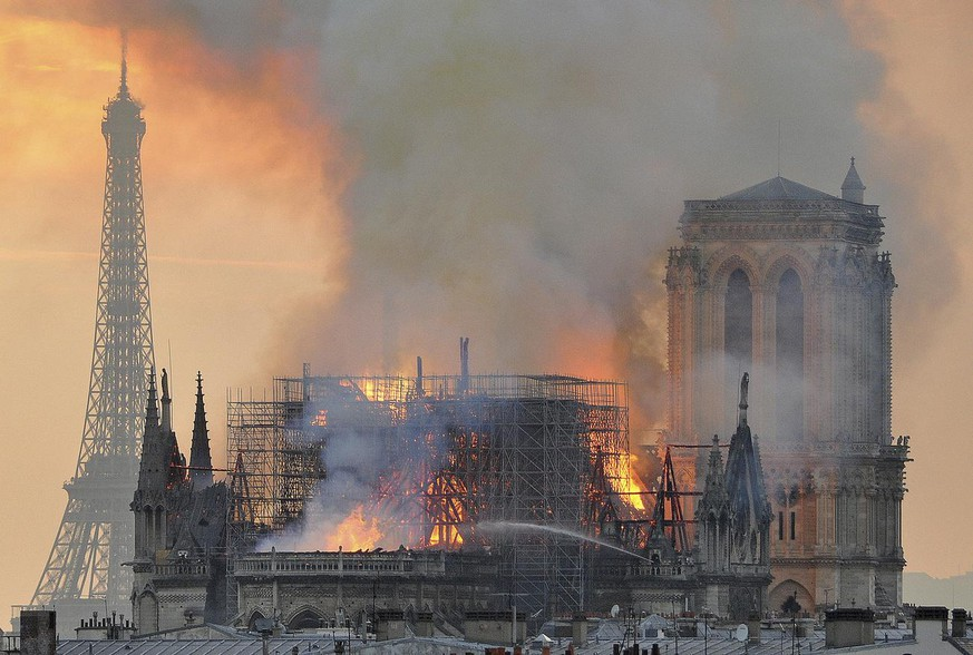 In this image made available on Tuesday April 16, 2019 flames and smoke rise from the blaze after the spire toppled over on Notre Dame cathedral in Paris, Monday, April 15, 2019. An inferno that raged through Notre Dame Cathedral for more than 12 hours destroyed its spire and its roof but spared its twin medieval bell towers, and a frantic rescue effort saved the monument's