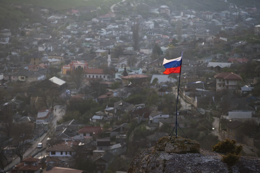 FILE - In this March 28, 2014 file photo, a Russian national flag flies on a hilltop near the city of Bakhchysarai, Crimea. The Group of Seven major industrialized countries on Thursday March 18, 2021, issued a strong condemnation of what it called Russia's ongoing
