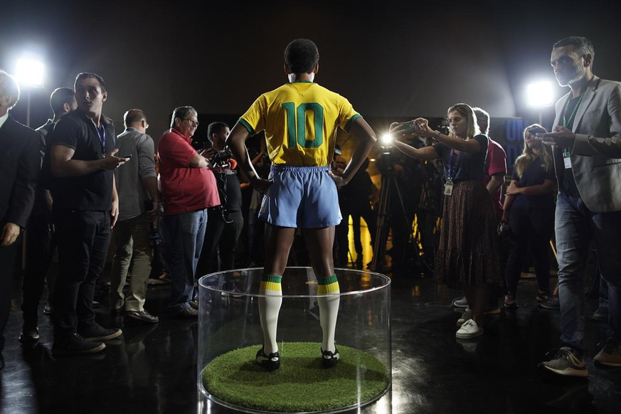 Journalists stand around the statue of legendary Brazilian player Pele at the Brazilian Soccer Team Museum in Rio de Janeiro, Brazil, Thursday, Feb. 20, 2020. The Brazilian Football Confederation unveiled the statue as part of commemorations of 50 years since the World Cup victory in 1970. (AP Photo/Leo Correa)