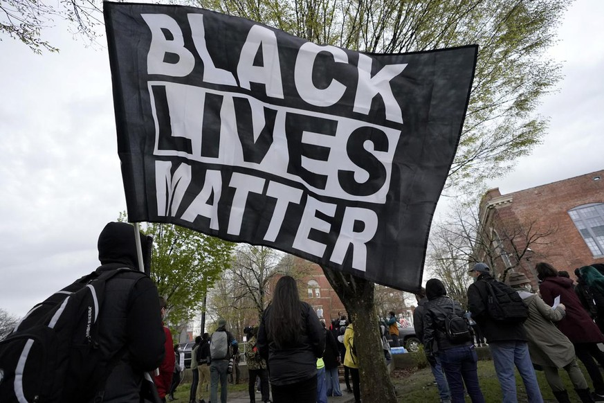 A demonstrator display a banner during a protest, Wednesday, April 21, 2021, in the Nubian Square neighborhood, of Boston, a day after a guilty verdict was announced at the trial of former Minneapolis police officer Derek Chauvin for the 2020 death of George Floyd. Chauvin has been convicted of murder and manslaughter in the death of Floyd. The demonstrators called for police reforms and racial equality. (AP Photo/Steven Senne)
