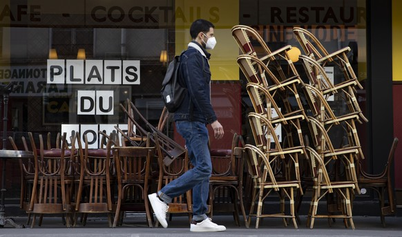 epaselect epa09144744 A pedestrian wearing a protective face mask walks past cafe terrace with chairs stacked outside a restaurant, in Paris, France, 19 April 2021. French President Emmanuel Macron announced on 15 April that he plans to allow cafe, bar and restaurant terraces along with museums to be the first to reopen as of mid-May, although no precise date was given. France's cultural and hospitality sectors are among the hardest affected by repeated and prolonged lockdown closures due to the coronavirus pandemic. Macron also stated that elementary schools would reopen as early as 26 April, regardless of the health crisis.  EPA/IAN LANGSDON