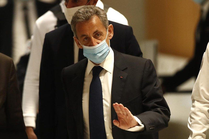 Former French President Nicolas Sarkozy arrives at the courtroom Monday, March 1, 2021 in Paris. The verdict is expected in a landmark corruption and influence-peddling trial that has put French former President Nicolas Sarkozy at risk of a prison sentence if he is convicted. Sarkozy, who was president from 2007 to 2012, firmly denied all the allegations against him during the 10-day trial that took place at the end of last year. (AP Photo/Michel Euler)
