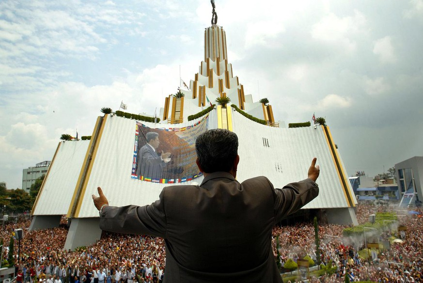 A Light of the World Church leader, Samuel Joaquin Flores, greets people from his balcony during the 'Holy Convocation' of the Light of the World Church at La Hermosa Provincia, Thursday, Aug. 11 2005, in Guadalajara City, Mexico. Every year some 300 thousend delegates come to Guadalajara City for the 'Holy Convocation' celebration. The Light of the World Church, who has a Christian origin, was found in Guadalajara City on Dec. 12, 1926 by Aaron Joaquin Gonzalez and actually has more than 5 million parishioners in 40 countries worldwide. (AP Photo/Guillermo Arias)
