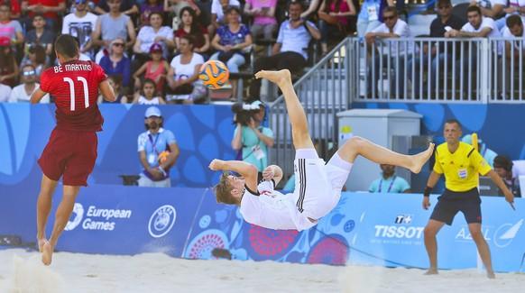 epa04816785 Glenn Hodel (C) of Switzerland in action during the Beach Soccer group A match between Portugal and Switzerland at the Baku 2015 European Games in Baku, Azerbaijan, 24 June 2015.  EPA/SRDJAN SUKI