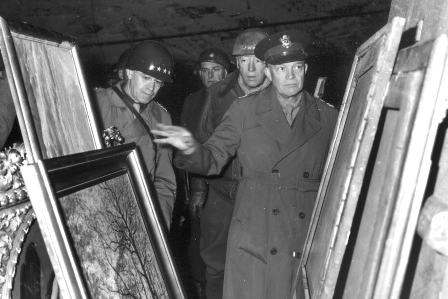 Gen. Dwight D. Eisenhower, center, inspects paintings in a salt mine at Merkers, near Gotha, Germany where the Nazi government stored art treasures and gold,  plundered in occupied countries in this April 12, 1945 photo. The Supreme Allied Commander is accompanied by  Gen. Omar N. Bradley, left,  and Lt. Gen. George Patton Jr., standing immediately behind him. (KEYSTONE/AP Photo/Str)  ===  ===