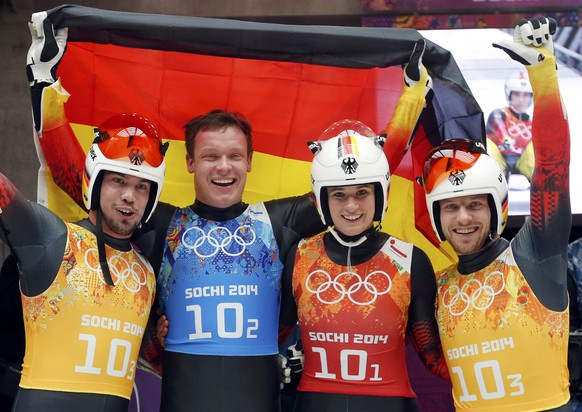 Germany's Tobias Arlt, Felix Loch, Natalie Geisenberger and Tobias Wendt (L-R) pose with their national flag during the luge team relay competition at the 2014 Sochi Winter Olympics February 13, 2014.      REUTERS/Fabrizio Bensch (RUSSIA  - Tags: OLYMPICS SPORT LUGE)