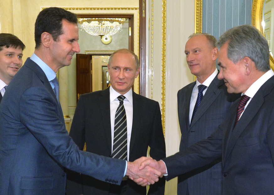 In this photo taken on Tuesday, Oct. 20, 2015, Syrian President Bashar Assad, second left, shakes hand with Russian Defense Minister Sergei Shoigu, as Russian President Vladimir Putin, center, looks on in the Kremlin in Moscow, Russia. President Bashar Assad was in Moscow, in his first known trip abroad since the war broke out in Syria in 2011, to meet his strongest ally Russian leader Putin. The two leaders stressed that the military operations in Syria - in which Moscow is the latest and most powerful addition- must lead to a political process. (Alexei Druzhinin, RIA-Novosti, Kremlin Pool Photo via AP)
