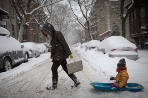 A woman pulls her child in a sled through the snow during the morning commute in the Park Slope area of the Brooklyn borough of New York February 13, 2014. A deadly winter storm moved north along theEast Coast of the United States on Thursday, bringing heavy snow, sleet and rain across the Washington, D.C., and New York areas, grounding flights and shutting government offices. REUTERS/Brendan McDermid (UNITED STATES - Tags: ENVIRONMENT)