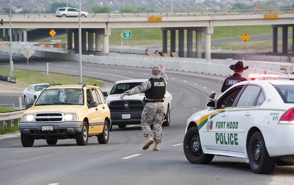 epa04151866 Military police direct traffic outside Fort Hood military base near Killeen, Texas, USA, 02 April 2014. Four people were reported to have been killed and 14 injured in a shooting at the US Army base and the base remains on lockdown as military police went building to building searching for others involved. The shooter was among the four dead, said US Representative Mike McCaul, chairman of the House Committee on Homeland Security.  EPA/ASHLEY LANDIS