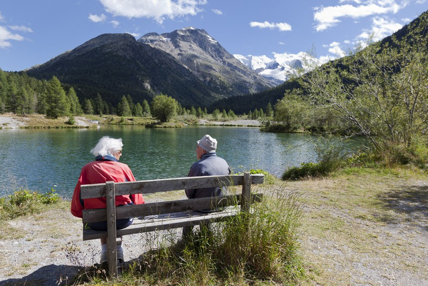 An elderly couple sitting on a bench at a lake near