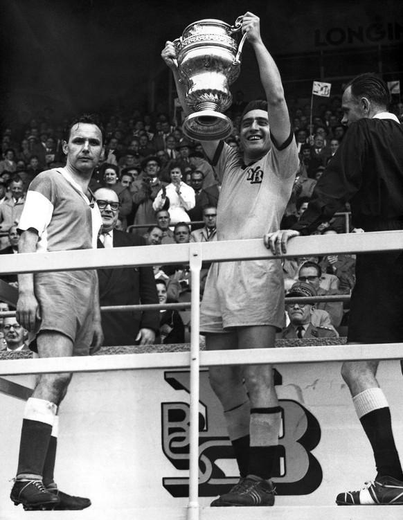"""Eugen """"Geni"""" Meier, Captain der Berner Young Boys, haelt die gewonnene Trophaee in die Hoehe, links steht der Captain der Grasshoppers, Bouvard, und rechts Schiedsrichter Mellet, aufgenommen im April 1958 in Bern, als YB Cupsieger wurde. Der 42-fache Schweizer Altinternationale Eugen 'Geni' Meier ist am Dienstag, 26. Maerz 2002 im Alter von 72 Jahren in Bern nach langer Krankheit gestorben. Nach Abschluss seiner Spielerkarriere stellte Meier sein immenses fussballerisches Wissen als Trainer zur Verfuegung. (KEYSTONE/STR)  ===  ==="""