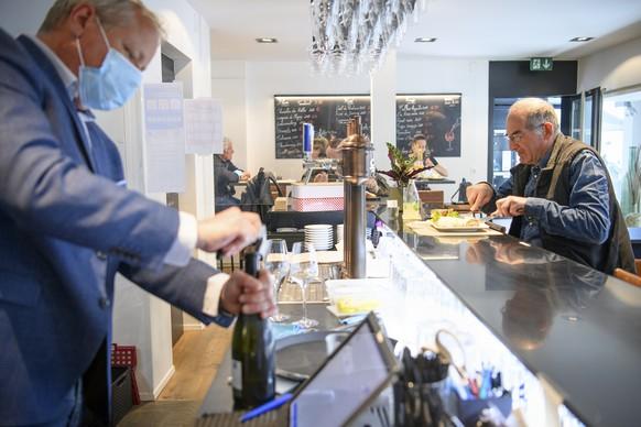 """A man eats his lunch inside the restaurant """"Le 23.6"""" the opening day of restaurants, during the coronavirus disease (COVID-19) outbreak in Porrentruy, Switzerland, Monday, May 31, 2021. (KEYSTONE/Laurent Gillieron).Un homme mange le repas de midi a l'interieur du restaurant """"Le 23.6"""" lors de la reouverture des restaurants lors de la pandemie de Coronavirus (Covid-19) ce lundi 31 mai 2021 a Porrentruy. (KEYSTONE/Laurent Gillieron)"""