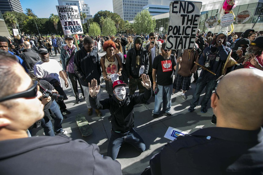 People protest against the killing of a homeless man by police outside LAPD headquarters in Los Angeles, California March 3, 2015. Los Angeles police officers trying to subdue a robbery suspect in the city's skid row section shot and killed the man as he tried to grab an officer's gun during a scuffle that was captured on video, police said on Monday. The dead man was reported by the Los Angeles Times to have been a homeless man known by his street name, Africa, who according to witnesses at the scene had been living in a tent for a few months after a period in a mental health facility. REUTERS/Lucy Nicholson (UNITED STATES - Tags: CRIME LAW CIVIL UNREST)
