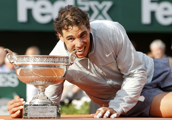 Rafael Nadal of Spain bites the trophy as he poses during the ceremony after defeating Novak Djokovic of Serbia during their men's singles final match to win the French Open Tennis tournament at the Roland Garros stadium in Paris June 8, 2014.                   REUTERS/Jean-Paul Pelissier (FRANCE  - Tags: SPORT TENNIS)