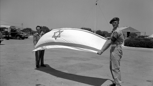 ARCHIV - ZUM 70. JAHRESTAG DER GRUENDUNG ISRAELS AM MONTAG, 14. MAI 2018, STELLEN WIR IHNEN FOLGENDES BILDMATERIAL ZUR VERFUEGUNG - Held by a Haganah military policeman and an unidentified Jewish official, the flag of the newly proclaimed Jewish state of Israel bellies in the breeze before it it hoisted over the Haifa Airport in this May 15, 1948 photo. (KEYSTONE/AP Photo)