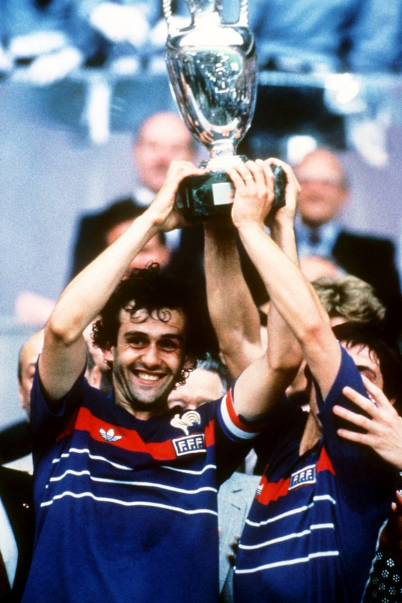 Frankreichs Mittelfeldregisseur und Kapitaen Michel Platini, links, und sein Teamgefaehrte Alain Giresse halten am 27. Juli 1984 im Pariser Prinzenpark-Stadion jubelnd den Henri-Delaunay-Pokal hoch. Frankreich gewinnt das Europameisterschafts-Endspiel gegen Spanien mit 2:0 und wird erstmals Europameister. (KEYSTONE/EPA PHOTO/DPA/Peter Robinson)