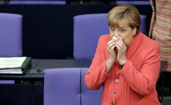 German Chancellor Angela Merkel blows her nose prior to a meeting of the German federal parliament, Bundestag, in Berlin, Germany, Thursday, June 18, 2015. (AP Photo/Michael Sohn)