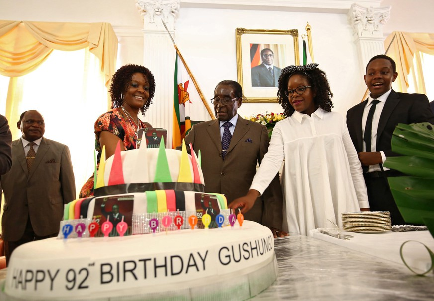 epa05175244 Zimbabwean President Robert Mugabe (C) with his wife Grace (2-L) and children Bona (2-R) and Chatunga (R) cut a piece of cake during his birthday event at state house in Harare, Zimbabwe, 22 February 2016. Mugabe, who has been ruling the country since 1987, turned 92 on 21 February 2016. Major birthday celebrations at costs of 800,000 US dollars are set for 27 February in Masvingo, a province that has been ravaged by a severe drought.  EPA/AARON UFUMELI