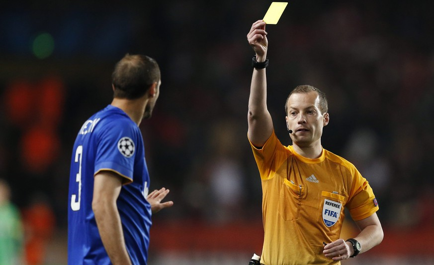epa04716587 Referee William Collum (R) of Scothland shows the yellow card to Giorgio Chiellini (L) of Juventus FC during the UEFA Champions League quarter final second leg soccer match between AS Monaco and Juventus FC at Louis II Stadium, in Monaco, 22 April 2015.  EPA/GUILLAUME HORCAJUELO