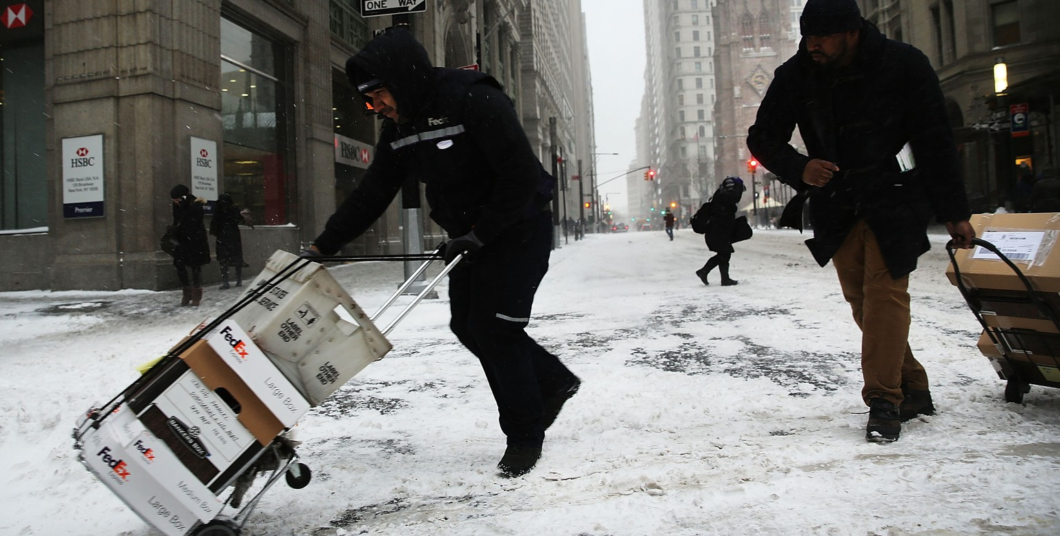NEW YORK, NY - JANUARY 26:  Men delivering mail struggle in blowing snow during heavy snow in the financial district of Manhattan on January 26, 2015 in New York City. New York, and much of the Northeast, is bracing for a major winter storm which is expected to bring blizzard conditions and 18 to 24 inches of snow to the area. New York Mayor Bill de Blasio has announced that only emergency vehicles will be allowed on area roads after 11pm.  (Photo by Spencer Platt/Getty Images)