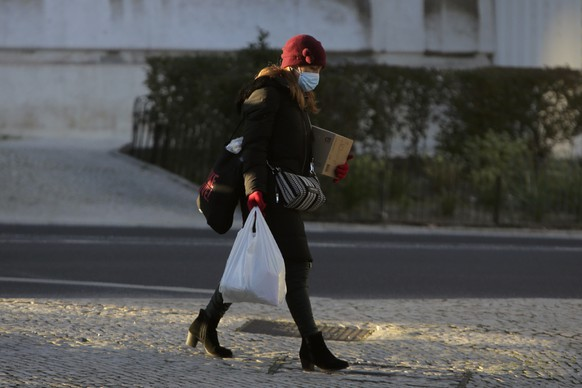 A woman wearing a face mask walks down a street in Lisbon, Monday, Jan. 11, 2021. The COVID-19 pandemic is quickly worsening in Portugal with authorities reporting new daily highs of cases and deaths and record hospitalizations. The heavy strain being placed on the public health service has prompted the government to consider a full lockdown. (AP Photo/Armando Franca)