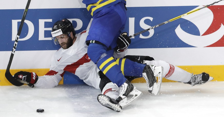 Sweden's John Klingberg, front, checks Switzerland's Dominik Schlumpf, back, during the Ice Hockey World Championships quarterfinal match between Switzerland and Sweden in the AccorHotels Arena in Paris, France, Thursday, May 18, 2017. (AP Photo/Petr David Josek)