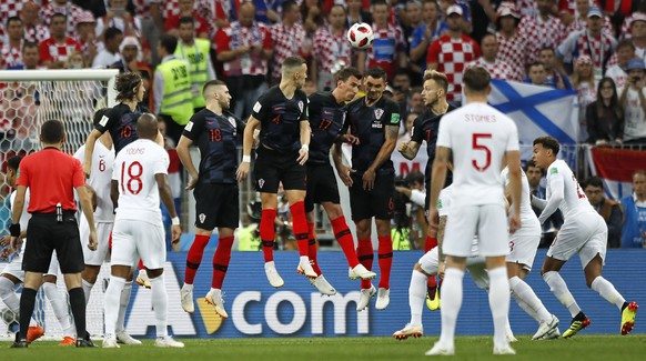 Croatia's defense jumps for a free kick by England's Kieran Trippier who scores the opening goal during the semifinal match between Croatia and England at the 2018 soccer World Cup in the Luzhniki Stadium in Moscow, Russia, Wednesday, July 11, 2018. (AP Photo/Matthias Schrader)