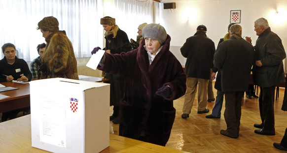 epa04541271 Croatian citizens cast their vote at a polling station during the Presidential Elections in Zagreb,Croatia 28 December 2014. Voting began in Croatia's presidential election, with incumbent Social Democrat Ivo Josipovic tipped to win another five-year term. Josipovic leads his main challenger, the conservative Kolinda Grabar Kitarovic, by 10 percentage points in opinion polls. The two other candidate have an outside chance of upsetting the front runners.  EPA/ANTONIO BAT