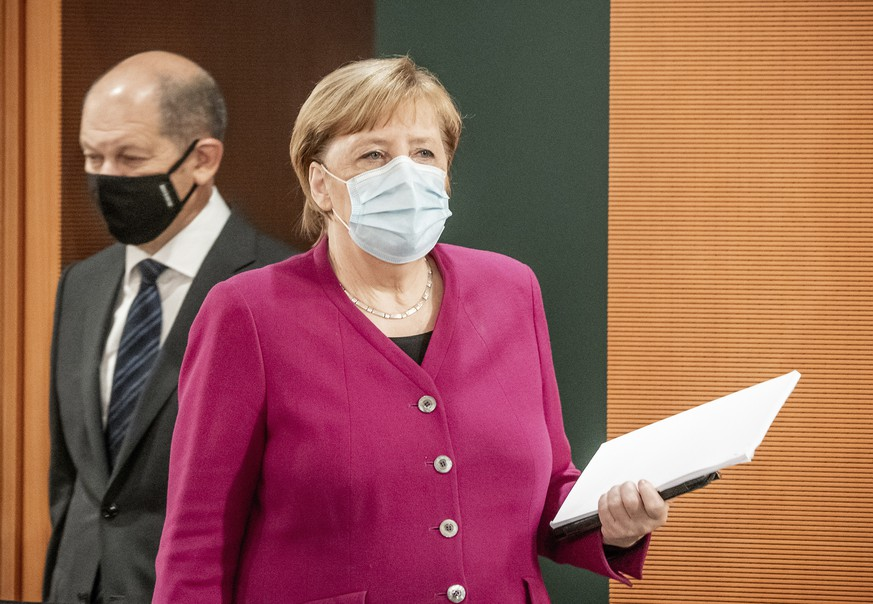 German Chancellor Angela Merkel, right, and Vice-Chancellor Olaf Scholz, left, wear face masks as they arrive for the weekly cabinet meeting at the Chancellery in Berlin, Germany, Wednesday, Oct. 14, 2020. (Michael Kappeler/DPA via AP, Pool)