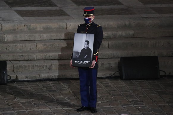 A Republican Guard holds a portrait of Samuel Paty in the courtyard of the Sorbonne university during a national memorial event, Wednesday, Oct. 21, 2020 in Paris. French history teacher Samuel Paty was beheaded in Conflans-Sainte-Honorine, northwest of Paris, by a 18-year-old Moscow-born Chechen refugee, who was later shot dead by police. (AP Photo/Francois Mori, Pool)