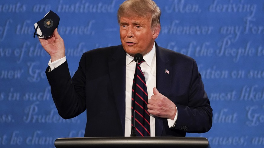 In this Sept. 29, 2020, file photo, President Donald Trump holds up his face mask during the first presidential debate at Case Western University and Cleveland Clinic, in Cleveland, Ohio. President Trump and first lady Melania Trump have tested positive for the coronavirus, the president tweeted early Friday. (AP Photo/Julio Cortez, File) Donald Trump