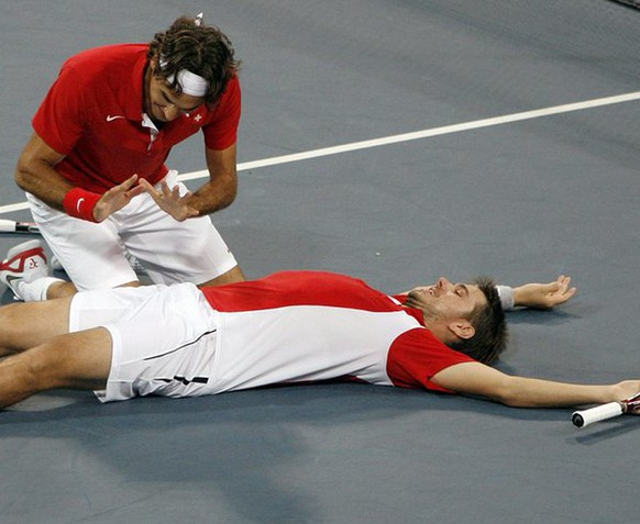 Roger Federer, left, and Stanislas Wawrinka of Switzerland react after winning their match against Bob Bryan and Mike Bryan during the semi final of the men's double tennis at the Beijing 2008 Olympics in Beijing, Friday, Aug. 15, 2008. (KEYSTONE/Peter Klaunzer)