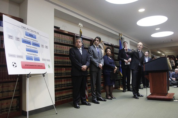 U.S. Attorney Kelly T. Currie of the Eastern District of New York, at podium, talks about an indictment against nine FIFA officials and five corporate executives for racketeering, conspiracy and corruption at a news conference, Wednesday, May 27, 2015, in the Brooklyn borough of New York. Attorney General Loretta E. Lynch is third from left. Nine of the 14 that were indicted by the Justice Department are soccer officials, while four are sports marketing executives and another works in broadcasting. (AP Photo/Mark Lennihan)