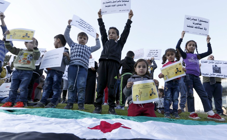 Syrian children carry placards as they call for the lifting of the siege off Madaya and Zabadani towns in Syria, in front of the offices of the U.N. headquarters in Beirut, Lebanon December 26, 2015. The placards read in Arabic: