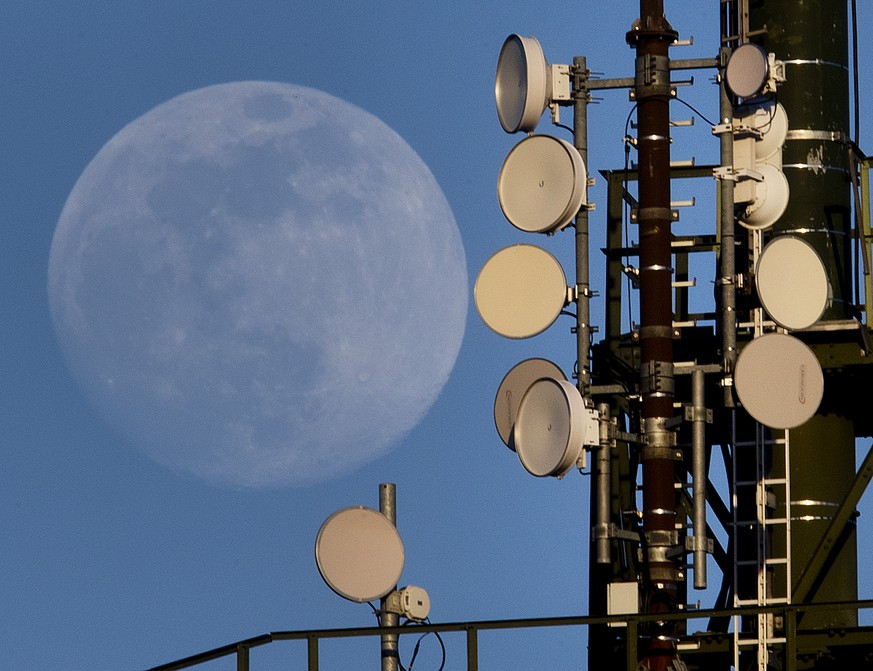 The moon rises behind a mobile radio mast in Wachenbuchen near Frankfurt, Germany, Tuesday, March 19, 2019.  Germany began auctioning frequencies for the future super-fast 5G network on Tuesday, amid frustration over conditions imposed by authorities and questions over whether China's Huawei can supply equipment. (AP Photo/Michael Probst)