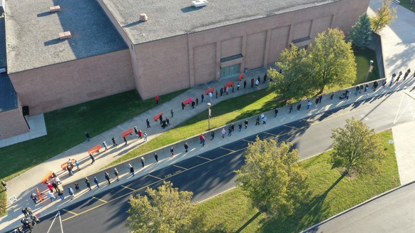 epa08795460 An image made with a drone shows a long line of voters waiting at a polling location at the Larry A Ryle High School in Union, Kentucky, USA, 03 November 2020. Americans vote on Election Day to choose between re-electing Donald J. Trump or electing Joe Biden as the 46th President of the United States to serve from 2021 through 2024.  EPA/MARK LYONS