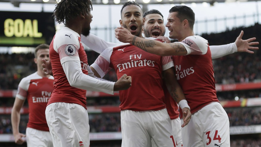 Arsenal's Pierre-Emerick Aubameyang, center, celebrates with his teammates after scoring his side's opening goal from a penalty spot during the English Premier League soccer match between Arsenal and Tottenham Hotspur at the Emirates Stadium in London, Sunday Dec. 2, 2018. (AP Photo/Tim Ireland)