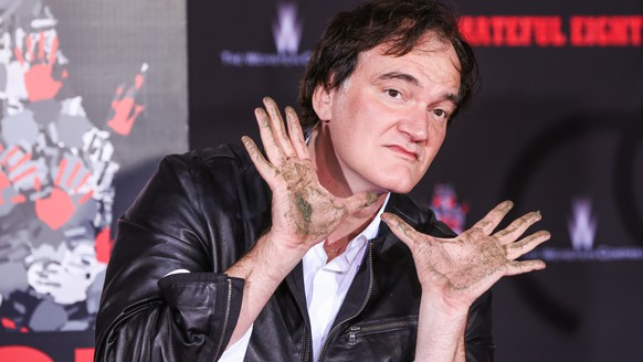 Quentin Tarantino poses with dirty hands at a hand and footprint ceremony at the TCL Chinese Theatre on Tuesday, Jan. 5, 2016, in Los Angeles. (Photo by Rich Fury/Invision/AP)