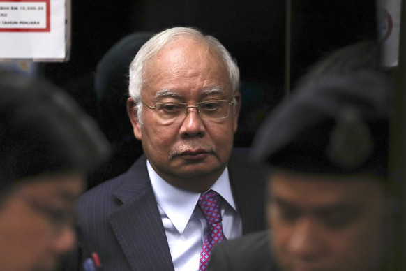 FILE - In this June 18, 2019, file photo, former Malaysian Prime Minister Najib Razak walks into the lift as he arrives at Kuala Lumpur High Court in Kuala Lumpur, Malaysia. Najib made a religious oath in a mosque Friday, Dec. 20, 2019, denying a new accusation that he ordered the killing of a Mongolian woman 13 years ago.(AP Photo/Vincent Thian, File) Najib Razak