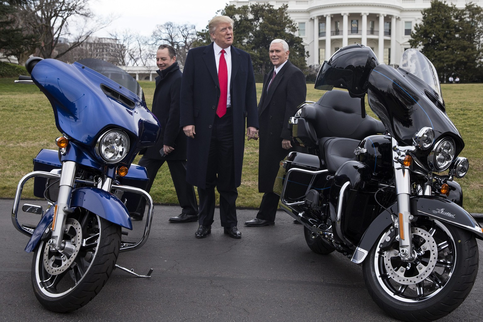 epa05767240 US President Donald J. Trump (C), US Vice President Mike Pence (R) and White House Chief of Staff Reince Priebus (L) look at Harley Davidson motorcycles while greeting Harley Davidson executives and union representatives on the South Driveway of the White House in Washington, DC, USA, 02 February 2017. President Trump and Vice President Mike Pence came out on the South Driveway to greet Harley Davidson executives and union representatives before a meeting in the White House.  EPA/MICHAEL REYNOLDS