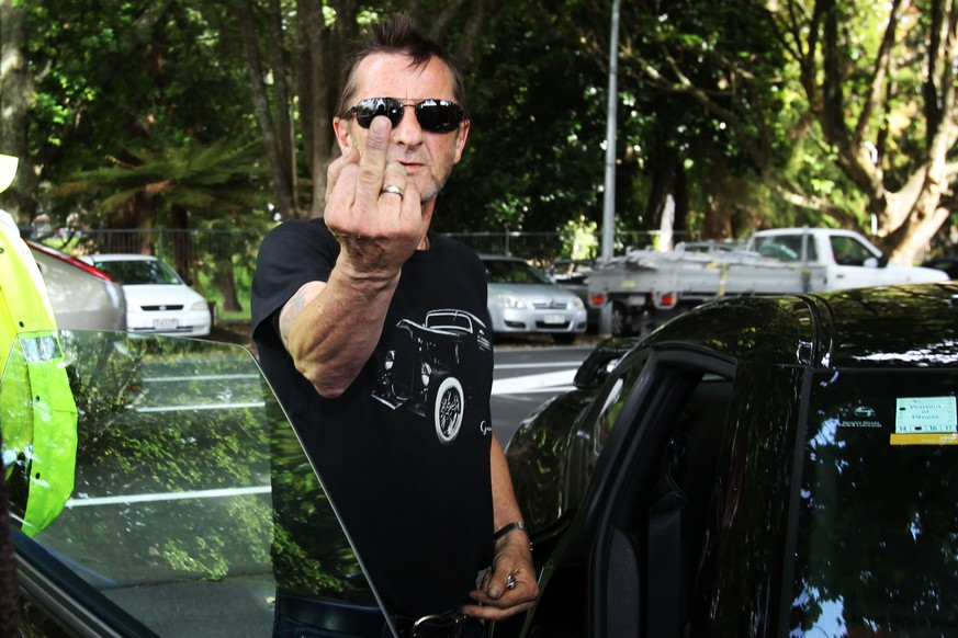 TAURANGA, NEW ZEALAND - NOVEMBER 26:  AC/DC drummer Phil Rudd gestures to members of the media after leaving Tauranga District Court after appearing in court after being charged with threatening to kill and possession of meth and marijuana at Tauranga District Court on November 26, 2014 in Tauranga, New Zealand.  Phil Rudd was ACDC's drummer from 1975 to 1983.  (Photo by Joel Ford/Getty Images)