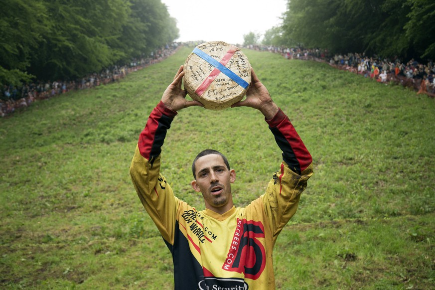 Chris Anderson, 30,  holds up his prize after breaking the all-time record for the most cheeses won in the death-defying Cheese Rolling Race, in Brockworth, Gloucestershire, England, Monday May 28, 2018. The champion cheese chaser has now taken home a total of 21 Double Gloucester cheeses over the past 14 years.  (Aaron Chown/PA via AP)