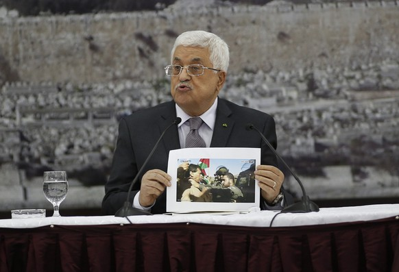 Palestinian President Mahmoud Abbas shows a picture of Palestinian minister Ziad Abu Ein as he is grabbed by an Israeli border policeman, during a meeting with the Palestinian leadership in the West Bank city of Ramallah December 10, 2014. Abu Ein died on Wednesday shortly after the Israeli border policeman shoved and grabbed him by the throat during the protest in the West Bank, an incident Abbas described as barbaric. Abu Ein, 55, a minister without portfolio, was among scores of Palestinian and foreign activists who were confronted at an Israeli checkpoint in the occupied Palestinian territory while heading to a demonstration against Jewish settlements. The Israeli military said in a statement it was investigating the circumstances that led to Abu Ein's death. REUTERS/Mohamad Torokman (WEST BANK - Tags: POLITICS CIVIL UNREST)