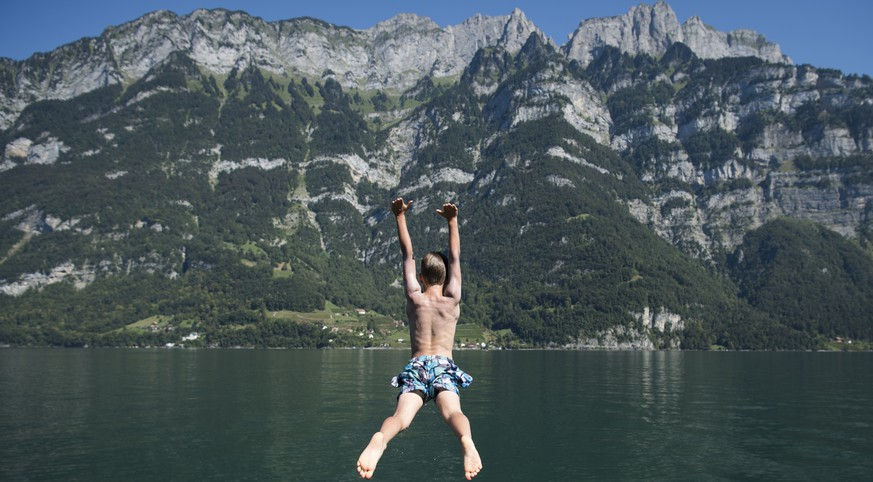 Jonas kuehlt sich ab mit einem Sprung ins Wasser, am Samstag, 27. August 2016, am Walensee in Murg. (KEYSTONE/Gian Ehrenzeller)  Jonas jumps in the water of the Walensee lake at Murg, Switzerland, Saturday, August 27, 2016. (KEYSTONE/Gian Ehrenzeller)