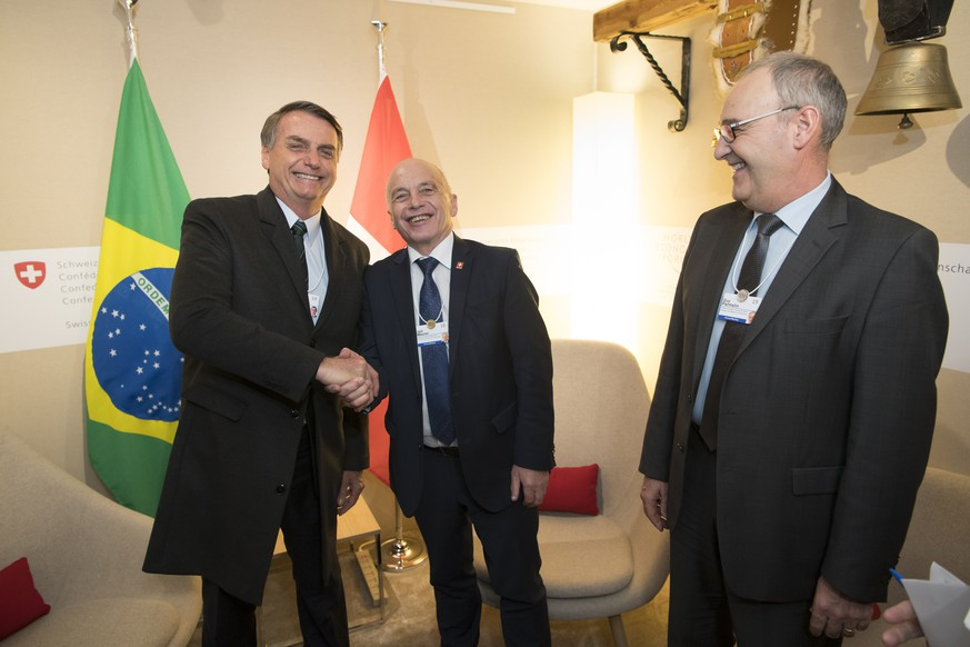 Brazil's President Jair Bolsonaro, left, shakes hands with Swiss Federal President Ueli Maurer, centre, next to Swiss Federal Councillor Guy Parmelin, right, during a bilateral meeting on the sideline of the 49th Annual Meeting of the World Economic Forum, WEF, in Davos, Switzerland, Wednesday, January 23, 2019. The meeting brings together entrepreneurs, scientists, corporate and political leaders in Davos under the topic