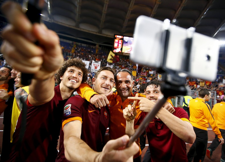 AS Roma's Francesco Totti (2nd L) takes a selfie with his team mates Alessandro Florenzi (R) and Salih Ucan (L) at the end of their Italian Serie A soccer match against Palermo at the Olympic stadium in Rome, Italy May 31, 2015. REUTERS/Tony Gentile      TPX IMAGES OF THE DAY
